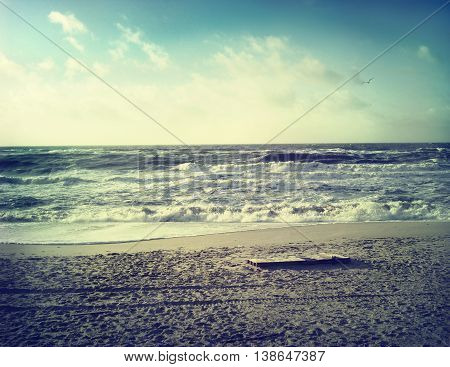 Beach scene with waves rolling in. Sepia toned image.