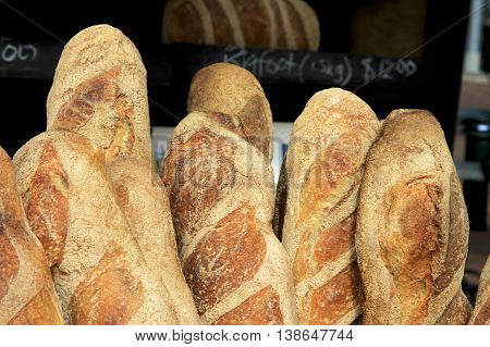 Freshly baked baguettes for sale in a community market.