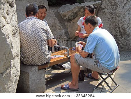 Chinese People Are Playing Cards In Park Of Chengdu