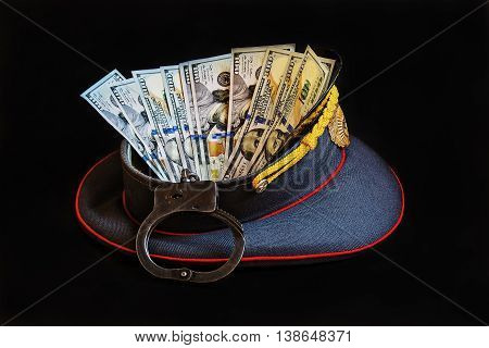 Abstract picture with the image of a police cap handcuffs and US currency