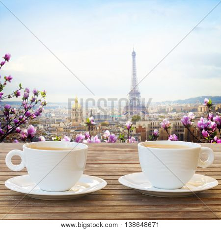 two cups of coffee in Paris cafe with view of parisian roffs and Eiffel Tower