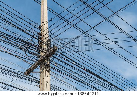 Electric pole and disorganized messy electricity line with against blue cloudy sky abstract background.