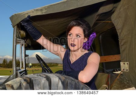 Retro style young woman in vintage military truck with Tongariro volcano in background (New Zealand scenery)