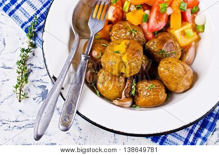 Young baked potatoes with garlic and thyme on a light background concrete. Selective focus.