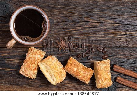Cup of hot coffee and puff cookies with cheese on dark wooden table top view