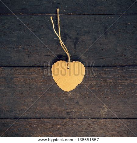 Blank Brown Tag Heart Shape On Old Wood Background With Space.