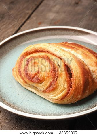 Sweet cinnamon pastry on a plate with a rustic wooden background