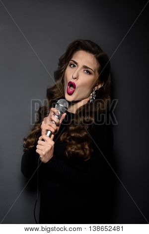 Portrait of beautiful karaoke lady singing in studio. Pretty woman with microphone posing in studio. Music and karaoke concepts.
