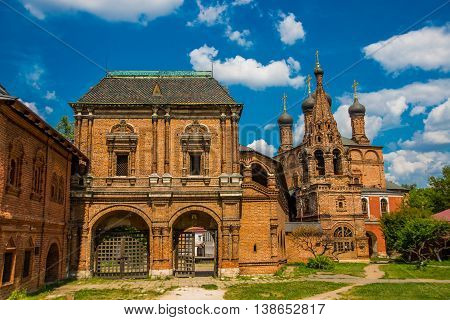 Krutitsy Patriarchal Metochion. The Old Brick Church On A Blue Sky With Clouds. Moscow, Russia.