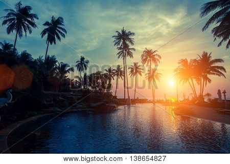 Sunset on the tropical coast, the silhouettes of the palm trees and pool.
