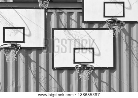 the abstract composition several of basketball baskets of monochrome tone of black white color is located on a wall of iron containers