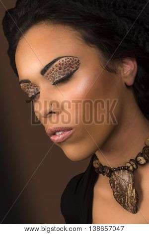 Beautiful young black woman with animal print eye shadow on closed eyes.