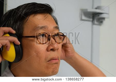 An acoustic engineer listening to the audio from a headset