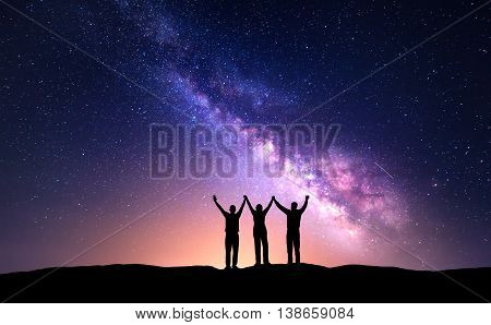 Night landscape with Milky Way and silhouette of people. Night starry sky with silhouette of happy friends with raised-up arms on the hill. Beautiful Universe. Astrophotography