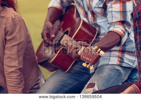 Closeup portrait of Afro-American man playing guitar while spending free time with his best friends on picnic. Picnic concept.