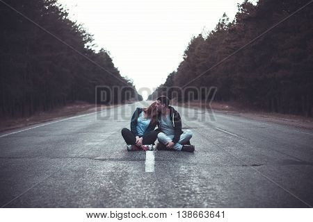 Photo of a boy and girl sits on a road