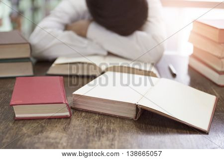 Man Sleeping On Book With Textbook Stack On Wooden Desk