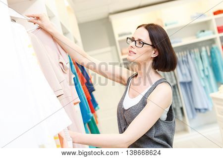 Joyful f shop assistant is working in boutique. She is taking hanger with clothing from rack. Woman is standing and smiling