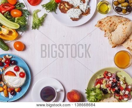Greek appetizers - fritters of zucchini with tzatziki sauce Greek salad yogurt with fresh fruit and nuts olives vegetables and herbs top view copy space.