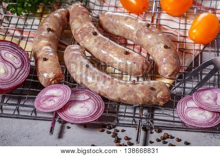 Raw sausages with vegetables and spices on the grill grate.