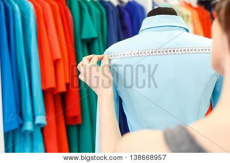 Skillful female designer is taking measurements of dress back on mannequin. Woman is standing in ateliers and holding tape-line with seriousness