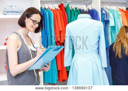 Skillful fashion designer is writing measurements of dress. She is holding folder and tape-line on neck. Woman is standing in shop and smiling