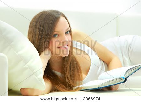 Full length of a young lady lying on sofa reading book