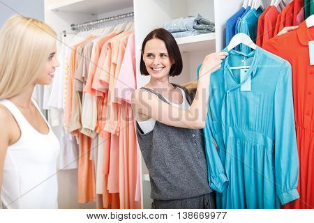 This dress might suit you. Joyful young shop assistant is holding clothing and smiling. She is looking at client with confidence