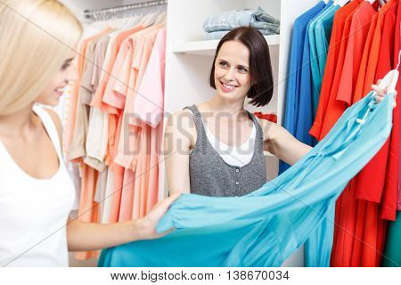Try on this dress. Cheerful young saleswoman is showing wear to customer in boutique. Woman is touching cloth and smiling with satisfaction