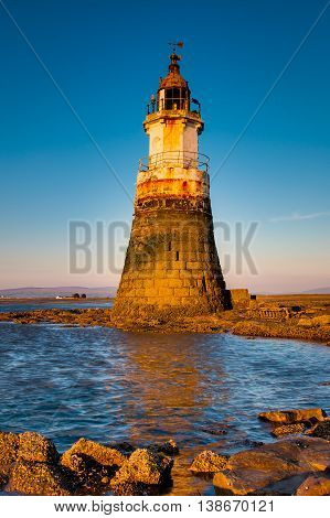 Plover Scar lighthouse at Cockerham on Morecambe Bay, Lancashire, UK. At sunset.