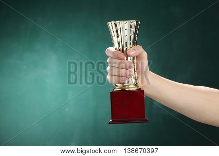 hand holding up a gold trophy cup on the blackboard