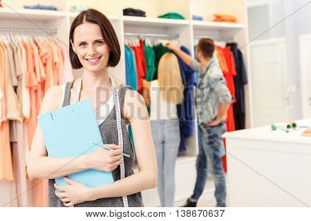 Confident shop assistant is working in boutique. She is standing and smiling. Woman is holding folder and looking at camera with joy. Couple is choosing clothing on background