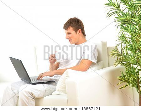 miling young man working on laptop computer at home