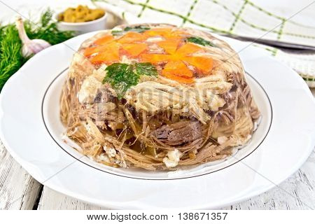Jellied pork and beef with carrots and parsley on a plate, towel, garlic, mustard and dill on the background light wooden boards