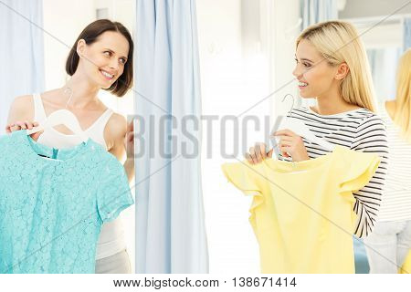 Two women are standing in changing room and holding up dresses. They are looking at each other with joy. Friends are smiling with happiness