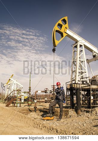 Man engineer in the oil field wearing red helmet and work clothes talking on the radio. Pump jack and wellhead background. Oil and gas concept. Toned.