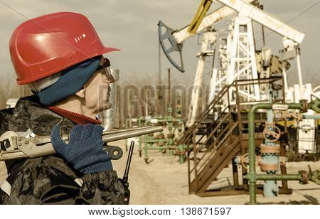Portrait of man engineer in the oil field wearing red helmet and work clothes holding wrenches in his hand and radio in jacket pocket. Blurry pump jack and wellhead background. Oil and gas concept. Toned.