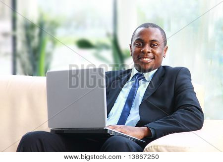Attractive African American smiling at computer, while sitting at a desk typing on keyboard. Square