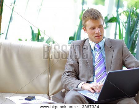 Casual looking businessman working on laptop computer in front of office window