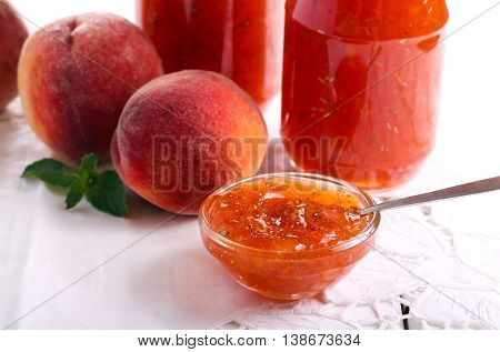 Peach and rosemary jam in small bowl and jars