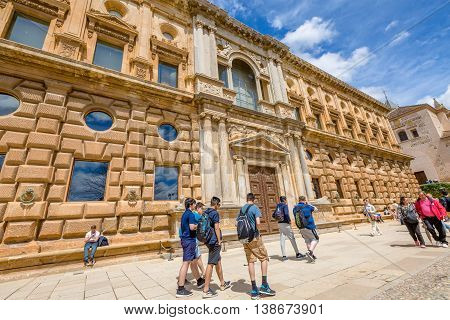 Alhambra of Granada, Andalucia, Spain - April 17, 2016: people walk in front of facade of Charles V Palace, a renaissance building, Unesco Heritage.