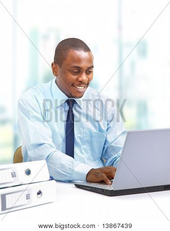 Retrato de un hombre de negocios joven guapo con un ordenador portátil
