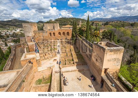 Granada, Spain - April 17, 2016: aerial view of people and tourists visiting the Alcazaba de Granada, the military fortress of Alhambra, one of the most visited attractions of Andalusia.