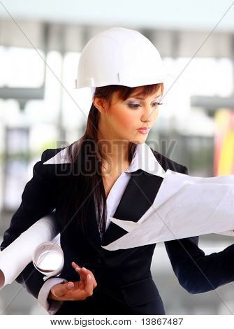 Smiling young female architect holding blueprints isolated on white background
