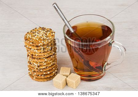 Stack of cookies with sesame seeds sugar and tea on wooden table