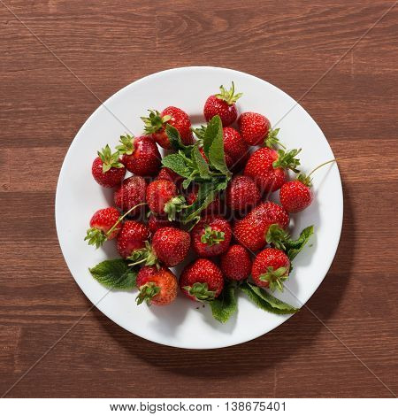Ripe red strawberries on wooden table. Strawberry. Fresh strawberry. Red strewberry. Strawberry Juice. Loosely laid strawberries in different positions.