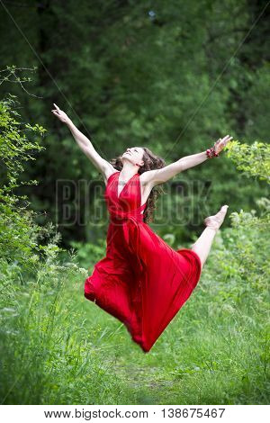 Happy beautiful young caucasian brunette woman in red dress jumping outdoors whole-length portrait