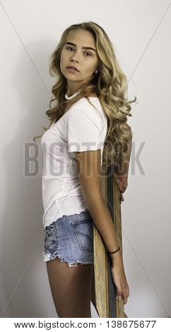 Beautiful blond girl wearing white shirt and jean shorts holding skateboard.