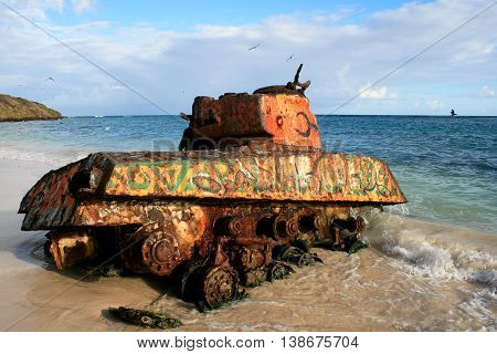 Old rusted and painted remnants of an US army tank on the Flamenco beach Culebra Island Puerto Rico