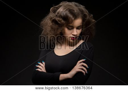 Portrait of beautiful lady with modern hairstyle posing with her arms crossed or folded while looking downwards.